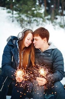 Heureux couple souriant avec des cierges de vacances célébrant noël à l'extérieur dans la forêt d'hiver