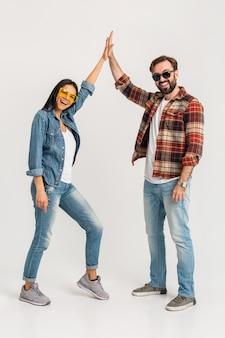 Heureux couple souriant donnant cinq gagnants équipe isolée sur studio blanc