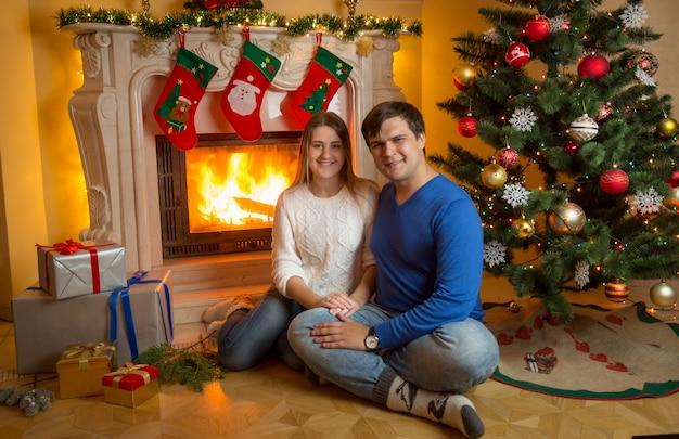 Heureux couple souriant posant une cheminée en feu avec des cadeaux de noël
