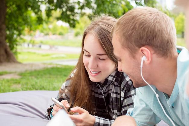 Heureux couple souriant, sortir à l'extérieur, couché sur un coussin et regarder le téléphone portable.