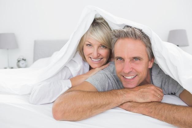 Heureux couple souriant sous les couvertures à la caméra