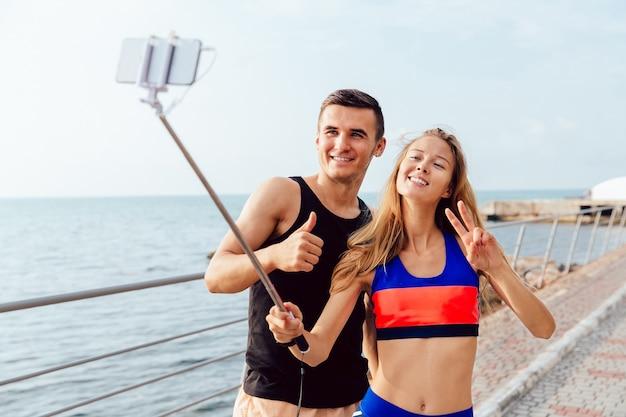 Heureux couple en sportswear montrant un pouce vers le haut et signe de paix tout en prenant un selfie