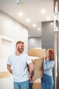 Heureux couple tenant des boîtes en carton et se déplaçant vers un nouvel endroit