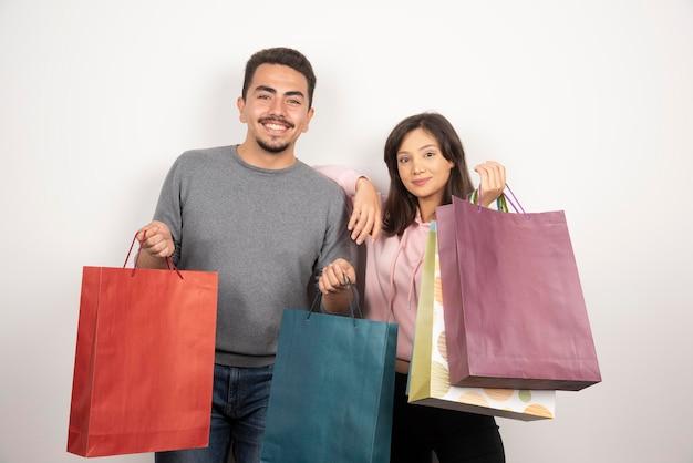 Heureux couple tenant des sacs à provisions ensemble.