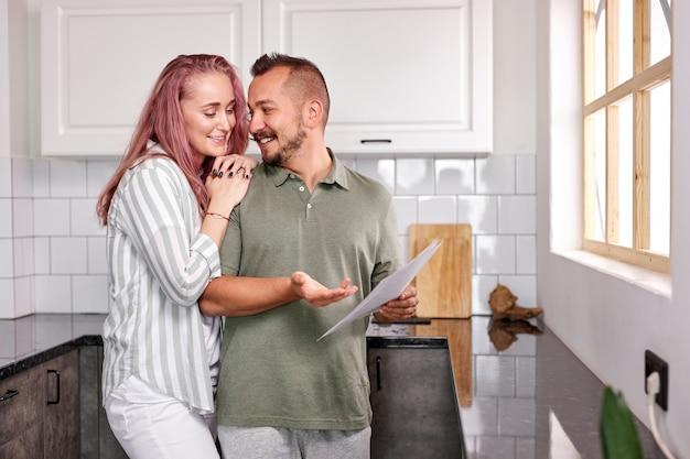 Heureux couple tenir des papiers, vérifier les factures de services publics ou les assurances. homme caucasien et femme ont parler, dans la cuisine