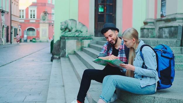 Heureux couple de touristes assis dans les escaliers de la rue vérifiant le plan de la ville et discutant