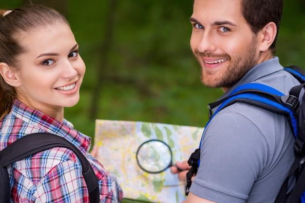Heureux couple de touristes. beau jeune couple d'amoureux portant des sacs à dos et regardant par-dessus l'épaule avec le sourire en marchant le long du sentier forestier