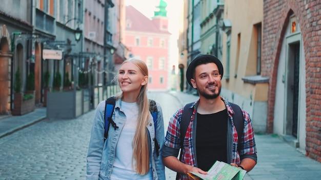 Heureux couple de touristes avec carte marchant dans la rue centrale de la vieille ville européenne, ils regardent autour de...