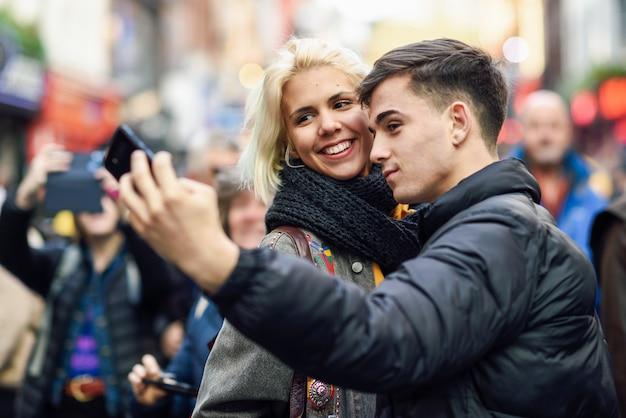 Heureux couple de touristes prenant selfie dans une rue bondée.