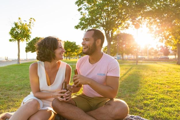 Heureux couple en train de bavarder autour d'une bouteille de bière