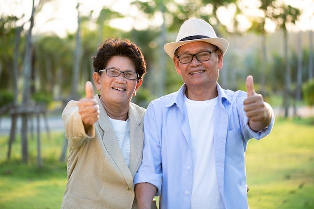 A, heureux, couples aînés, asiatique, vieil homme, et, femme, à, pouces haut, sourire
