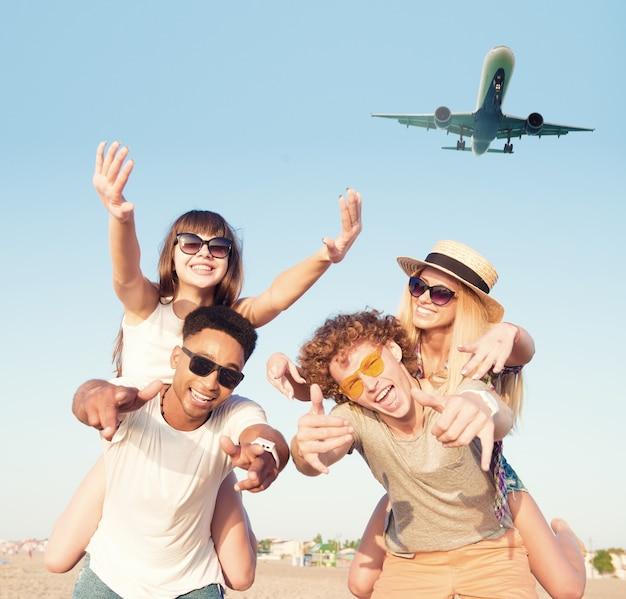 Heureux couples souriants jouant à la plage avec des avions dans le ciel