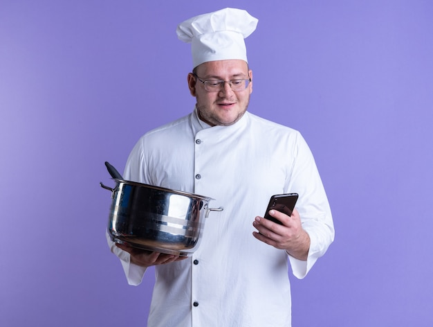 Heureux cuisinier mâle adulte portant un uniforme de chef et des lunettes tenant un pot et un téléphone portable regardant un téléphone portable isolé sur un mur violet