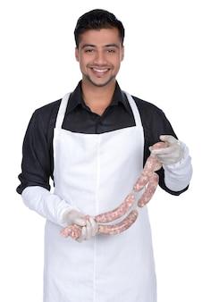 Heureux cuisinier tenant des saucisses et souriant.