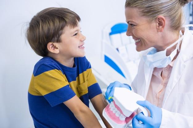 Heureux dentiste tenant le moule dentaire tout en regardant garçon