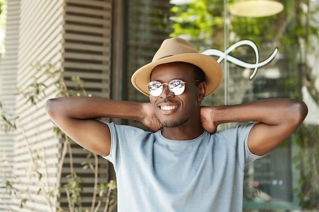 Heureux et détendu jeune étudiant masculin à la peau sombre dans des lunettes de soleil élégantes et des couvre-chefs gardant les mains derrière la tête et souriant largement, profitant des vacances d'été, déjeunant au restaurant sur le trottoir