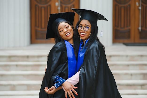 Heureux deux étudiants internationaux. l'obtention du diplôme de début d'études universitaires certificat de réussite concept de diplôme.