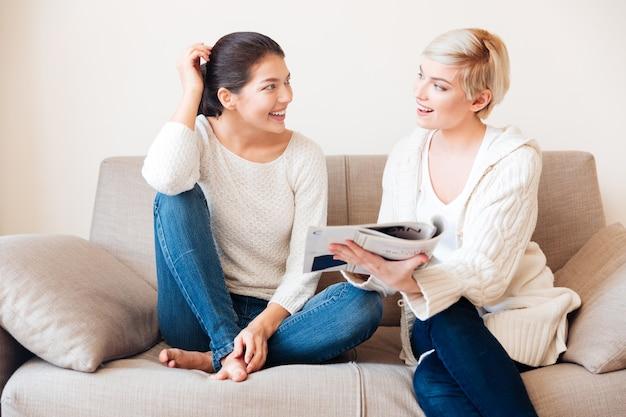 Heureux deux femmes lisant un magazine sur le canapé à la maison