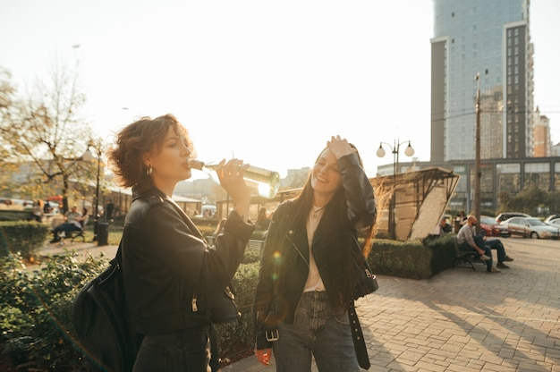 Heureux deux filles en vêtements décontractés se tiennent dehors au lever du soleil et boivent du vin dans des bouteilles