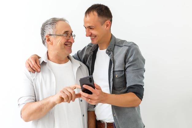 Heureux deux générations d'hommes de la famille vieux père embrassant un jeune fils adulte s'amusant à utiliser un téléphone intelligent en regardant une vidéo amusante sur les réseaux sociaux à l'aide d'applications mobiles