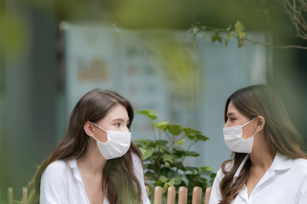 Heureux deux jeune femme avec un visage souriant portant un masque protecteur parler et rire avec communication mall