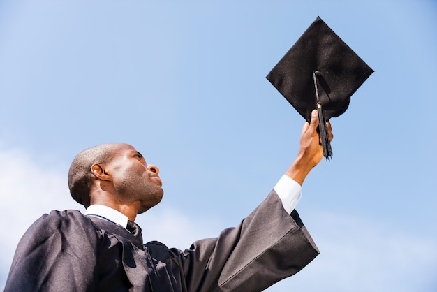 Heureux diplômé. low angle view of happy young african man in graduation gown tenant sa planche de mortier contre le ciel bleu