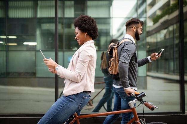 Heureux divers gens occupés utilisant des appareils technologiques en plein air en ville