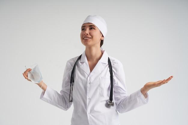 Heureux docteur heureux portant un masque facial regardant la mesure sur un thermomètre médical sur un mur blanc avec copie espace