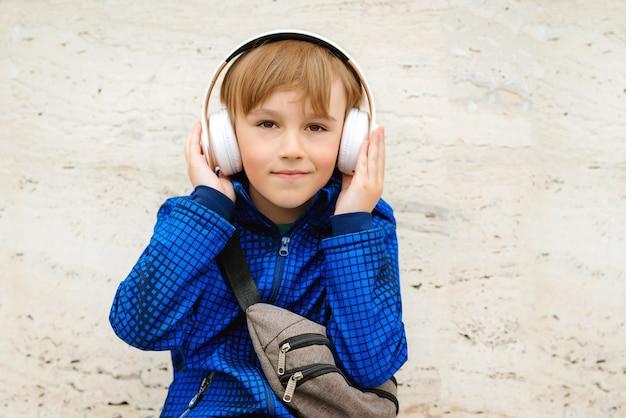 Heureux écolier mignon écoutant de la musique dans des écouteurs à l'extérieur de l'école.