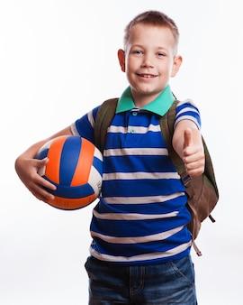 Heureux écolier avec sac à dos et ballon de football isolé sur blanc