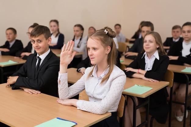 Heureux écoliers s'asseoir à un bureau dans la salle de classe