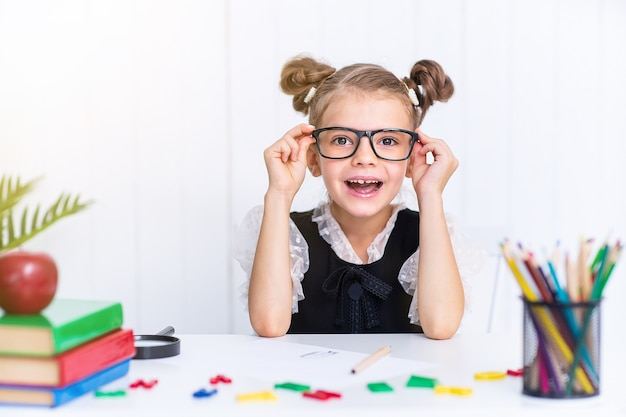 Heureux élève souriant au bureau. enfant dans la salle de classe avec des crayons, des livres. kid fille de l'école primaire.