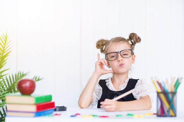 Heureux élève souriant au bureau pointant le doigt. fille dans la salle de classe avec des crayons, des livres. kid fille de l'école primaire.