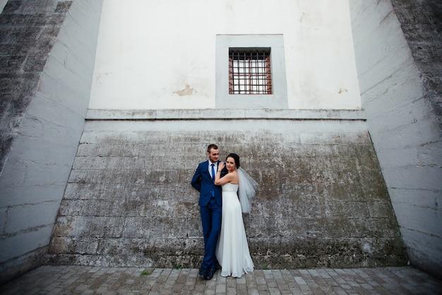 L'heureux embrasse sa mariée son amant sur un fond de mur gris