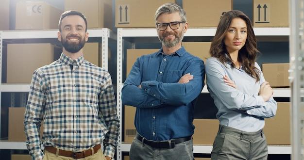 Heureux employés de poste masculins et féminins souriants debout dans le magasin de courrier, croisant les mains devant et souriant joyeusement