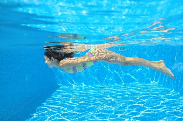 Heureux enfant actif nage sous l'eau dans la piscine