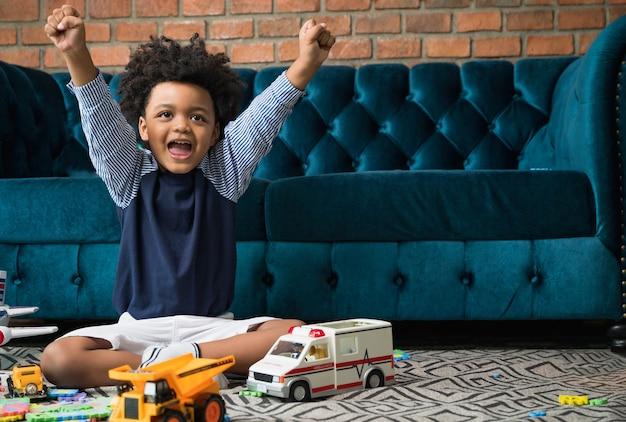 Heureux enfant afro-américain avec des jouets et un canapé à la maison