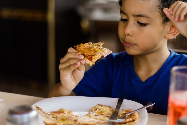 Heureux enfant afro-américain, manger de la pizza.