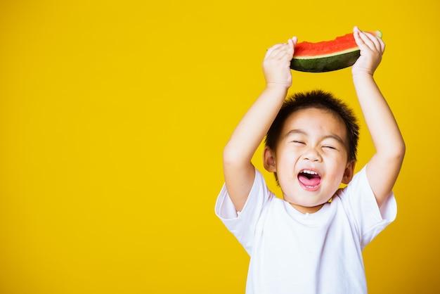 Heureux enfant asiatique petit garçon sourire détient pastèque coupée fraîche pour manger