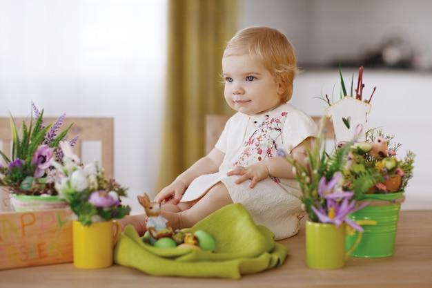 Heureux enfant assis à la table et tenant des oeufs de pâques
