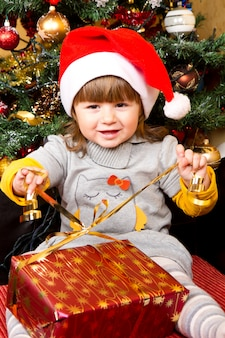 Heureux enfant au bonnet de noel ouvrant la boîte de cadeau de noël