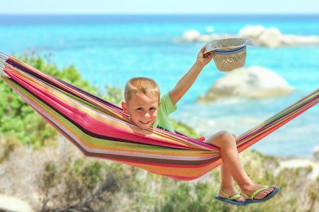 Heureux enfant au bord de la mer sur hamac