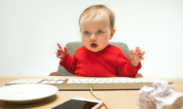 Heureux enfant bébé fille assise avec clavier d'ordinateur moderne ou ordinateur portable isolé sur un studio blanc