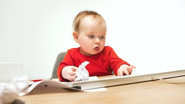 Heureux enfant bébé fille assise avec clavier d'ordinateur moderne ou ordinateur portable isolé sur un studio blanc.