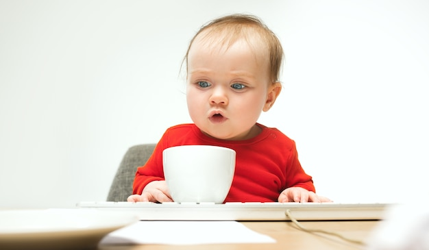 Heureux enfant bébé fille assise avec clavier d'ordinateur moderne ou ordinateur portable en studio blanc.