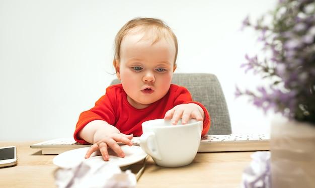 Heureux enfant bébé fille assise avec tasse et clavier d'ordinateur moderne ou ordinateur portable isolé sur blanc