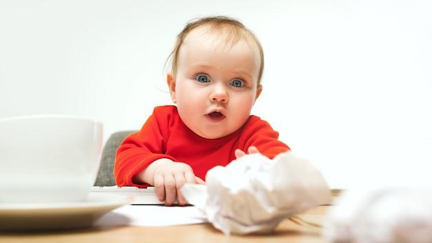 Heureux enfant bébé fille bambin assis avec clavier d'ordinateur isolé sur blanc