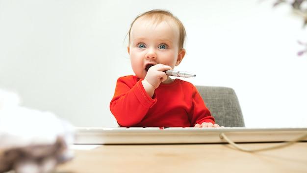 Heureux enfant bébé fille bambin assis avec clavier d'ordinateur isolé