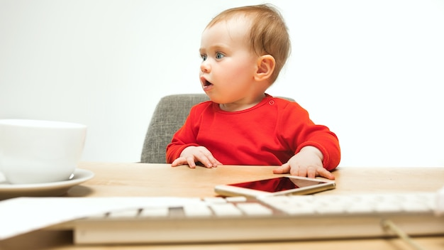 Heureux enfant bébé fille enfant assis avec le clavier de l'ordinateur isolé sur un blanc