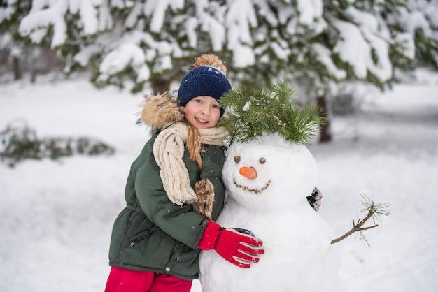 Heureux enfant blonde jolie fille plaing avec un bonhomme de neige sur une promenade d'hiver enneigée